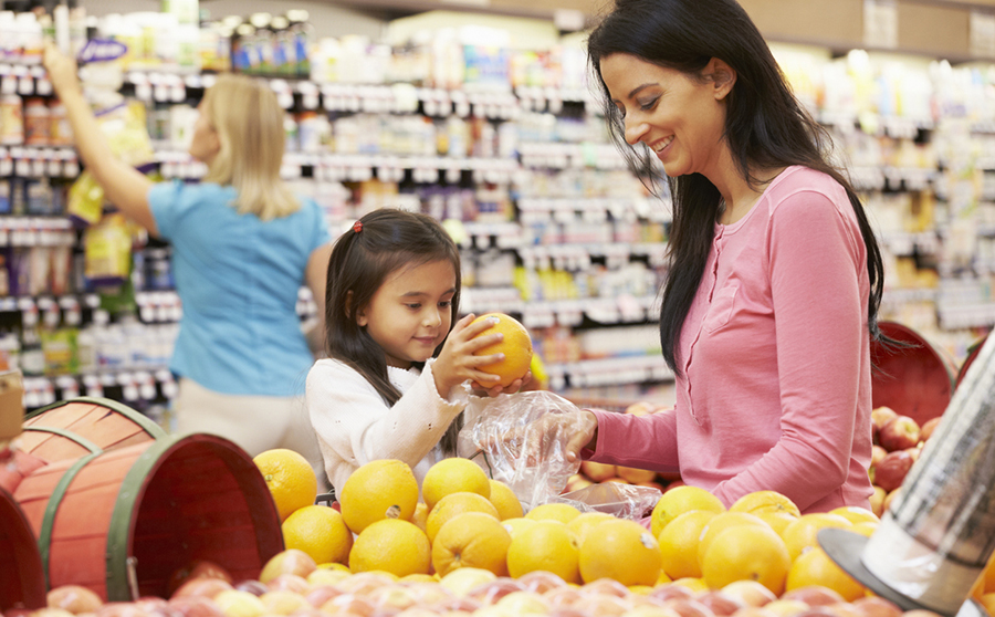 Mother And Daughter At Fruit Counter In Supermarket Putting Fruit Into A Bag